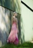 Schöne Blondine in rosa außerhalb eines rustikalen Gebäudes Lizenzfreie Stockbilder