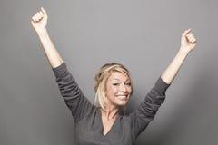 Schöne Blondine 20s, die Hände für Sieg anheben Stockbilder