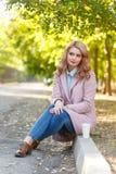 Schöne Blondine sitzt auf der Beschränkung im Park mit Kaffee Stockfotografie