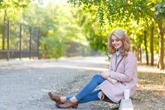 Schöne Blondine sitzt auf der Beschränkung im Park mit Kaffee Stockfoto