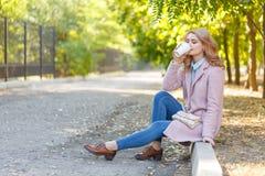 Schöne Blondine sitzt auf der Beschränkung im Park mit Kaffee Stockbild