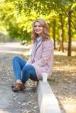 Schöne Blondine sitzt auf der Beschränkung im Park mit Kaffee Lizenzfreies Stockbild