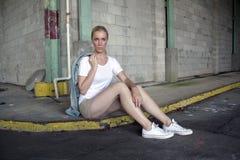 Schöne Blondine sitzt auf einer Straßenecke Stockbilder