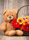 Schöne Blumen im Korb und in einem Teddybären Lizenzfreies Stockbild
