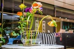 Schöne Blumen im ungewöhnlichen Glasvase in einem Innenraum von Wohnungen Ein Dekor für das Haus und das Büro betriebe Natürliche stockfoto
