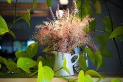 Schöne Blumen im Vase mit Licht von der Lampe Stockbild