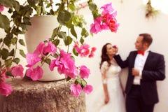 Schöne Blumen mit Braut und Bräutigam im Hintergrund Lizenzfreie Stockfotografie