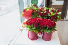 Schöne Blumensträuße von roten Rosen in der Geschenkbox, auf weißem Fensterbrett stockfotos