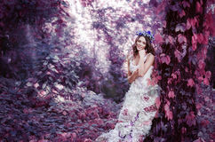 Schöne braunhaarige Frau in einem langen weißen Kleid, mit einem Kranz des Lavendels auf ihrem Kopf, ist im feenhaften Wald Lizenzfreie Stockfotos