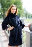 Schöne braunhaarige Frau in einem schwarzen Mantel stockfotografie