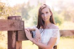 Schöne braunhaarige junge Frau am Bretterzaun Stockfotografie