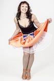 Schöne braunhaarige Künstlerin in chermnm Korsett mit Pailletten und orange Rock mit Gurt beugen Lizenzfreies Stockfoto