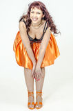 Schöne braunhaarige Künstlerin in chermnm Korsett mit Pailletten und orange Rock mit Gurt beugen Stockbild