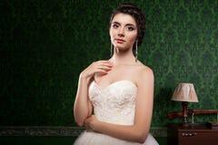 Schöne Braut auf grünem Weinlesemusterhintergrund Lizenzfreie Stockbilder