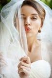 Schöne Braut beim Hochzeitskleider- und -schleierblinzeln, Kuss sendend Lizenzfreies Stockbild