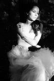 Schöne Braut, die auf Baum liegt und weg schaut Stockfotografie