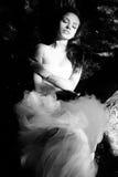 Schöne Braut, die auf Baum mit geschlossenen Augen liegt Stockfotografie