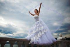 Schöne Braut, die auf die Terrasse mit Schleier geht Lizenzfreie Stockbilder