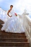 Schöne Braut, die auf Treppe am sonnigen Tag steht Stockbild