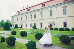 Schöne Braut, die in den Park nahe Schloss geht lizenzfreies stockfoto