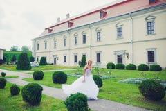 Schöne Braut, die in den Park nahe Schloss geht lizenzfreies stockbild