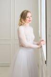 Schöne Braut, die am Fenster steht Stockfoto
