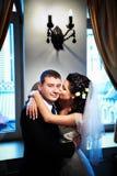 Schöne Braut, die ihren Bräutigam auf der Backe küßt Stockbild
