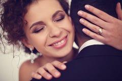 Schöne Braut, die ihren Bräutigam hält Lizenzfreie Stockbilder