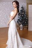 Schöne Braut, die im Studio mit verziertem Weihnachtsbaum aufwirft Stockfoto