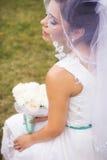 Schöne Braut, die sich vorbereitet, im weißen Kleid und im Schleier zu heiraten Stockfoto