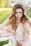 Schöne Braut draußen in einem Hochzeitskleid Lizenzfreies Stockfoto