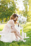 Schöne Braut draußen in einem Hochzeitskleid Stockfotografie