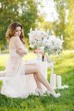 Schöne Braut draußen in einem Hochzeitskleid Lizenzfreie Stockfotografie