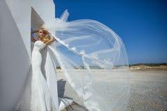 Schöne Braut in einem Hochzeitskleid in Griechenland mit einem langen Schleier Lizenzfreies Stockfoto