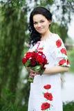 Schöne Braut in einem Kleid mit Stickerei lizenzfreies stockfoto