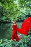 Schöne Braut in einem roten Hochzeitskleid Lizenzfreie Stockfotografie