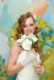 Schöne Braut in einem weißen Kleid mit einem Blumenstrauß von Callalilien Stockfoto