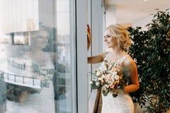 Schöne Braut in einem weißen Kleid steht nahe dem Fenster in einem Grossmarkt, blond stockbild