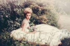 Schöne Braut in einem weißen Kleiderretrostil Stockfotografie