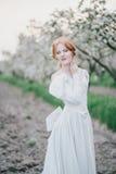 Schöne Braut in einem Weinlesehochzeitskleid, das in einem blühenden Apfelgarten aufwirft Set von 9 Abbildungen der wundervollen  Stockfoto