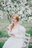 Schöne Braut in einem Weinlesehochzeitskleid, das in einem blühenden Apfelgarten aufwirft Set von 9 Abbildungen der wundervollen  Stockbild