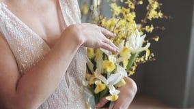 Schöne Braut hält einen bunten Blumenstrauß der Hochzeit stock footage