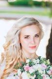 Schöne Braut Hochzeitsfrisur und bilden Junge Braut im Hochzeitskleid, das Blumenstrauß hält Stockbild