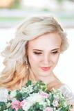 Schöne Braut Hochzeitsfrisur und bilden Junge Braut im Hochzeitskleid, das Blumenstrauß hält Stockfotografie