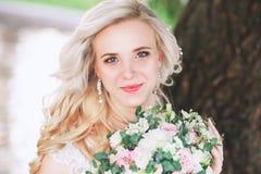 Schöne Braut Hochzeitsfrisur und bilden Junge Braut im Hochzeitskleid, das Blumenstrauß hält Lizenzfreies Stockfoto