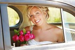 Schöne Braut im Auto auf Hochzeitstag Stockbilder