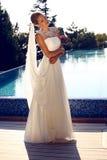 Schöne Braut im eleganten Hochzeitskleid, das neben einem Swimmingpool aufwirft Lizenzfreies Stockbild