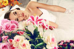 Schöne Braut im eleganten Hochzeitskleid, das unter Blumen aufwirft Stockfotos