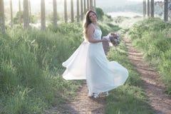 Schöne Braut im erstaunlichen Hochzeitskleid, das draußen in einen Wald tanzt Stockfotografie