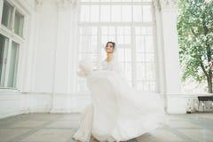 Schöne Braut im Hochzeitskleid mit langem Tellerrock, weißem Hintergrund, Tanz und Lächeln stockbild